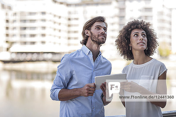 Businessman and woman having a meeting outdoors  using digital tablet