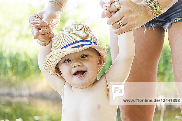 Portrait of laughing baby boy holding his mother's hands