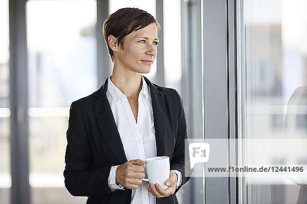 Businesswoman in office with cup of coffee looking out of window