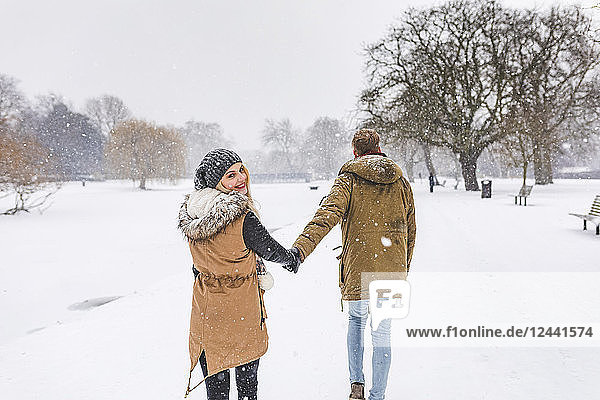 Happy teenage girl strolling with her boyfriend in park on snow day