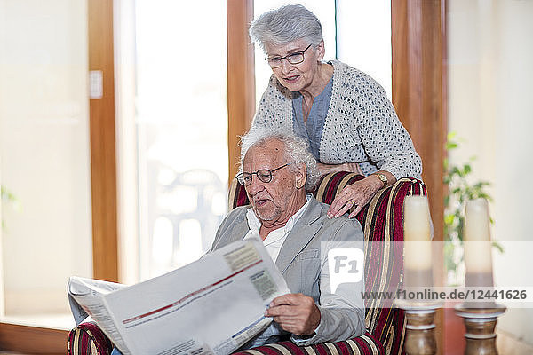 Senior man and woman sitting in library  reading newspaper