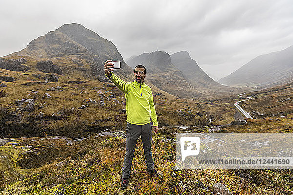 UK  Scotland  man in the Scottish highlands near Glencoe with a view on the Three Sisters taking a selfie