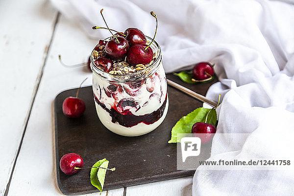 Glass of natural yoghurt with cherries  cherry jam and granola