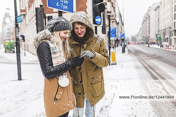 UK  London  young couple standing at roadside looking at cell phone on a snowy day