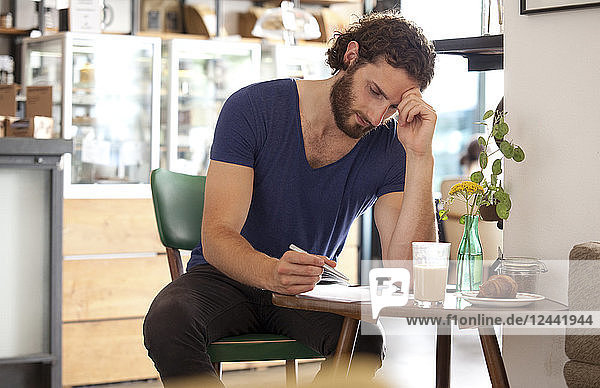 Pensive young man sitting in a coffee shop writing letter