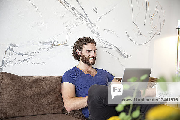 Smiling young man sitting on couch in a coffee shop using laptop