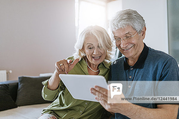 Happy senior couple at home sitting on couch sharing tablet