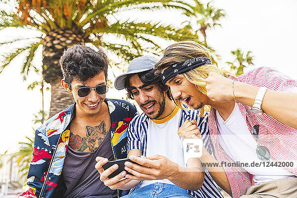 Portrait of three excited friends looking at cell phone