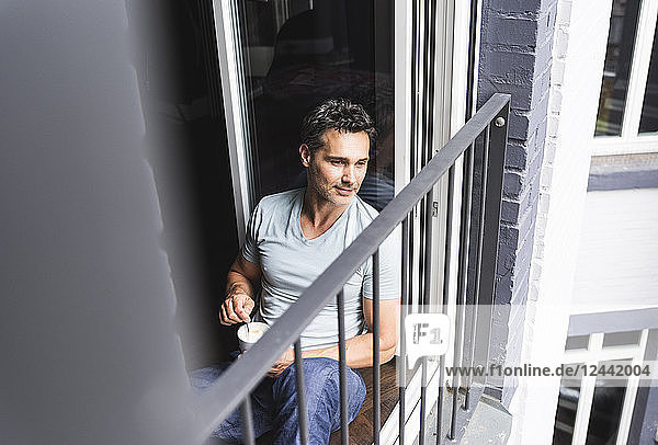 Man in pyjama at home with cup of coffee looking out of balcony door
