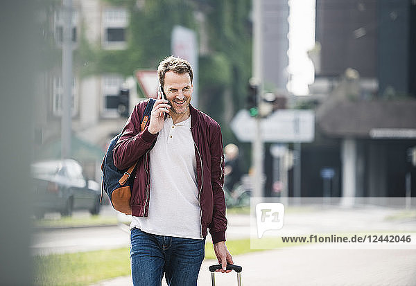 Smiling man with rolling suitcase on cell phone in the city