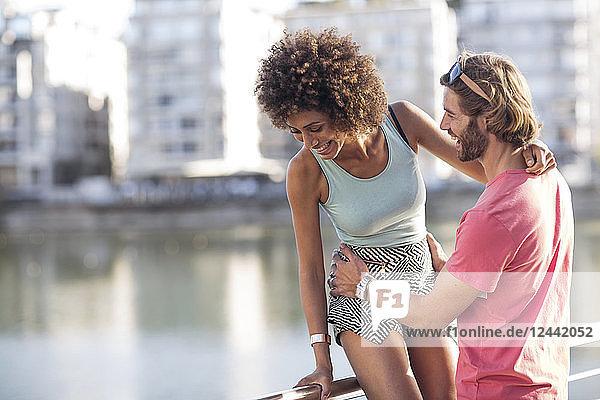 Happy couple standing at railing near water  having fun