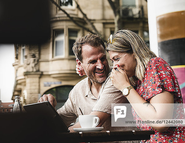 Happy couple with tablet at an outdoor cafe