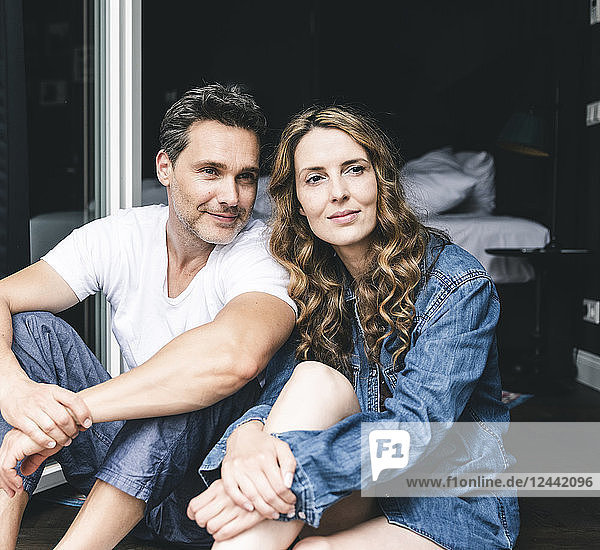 Smiling couple in nightwear at home sitting at French window