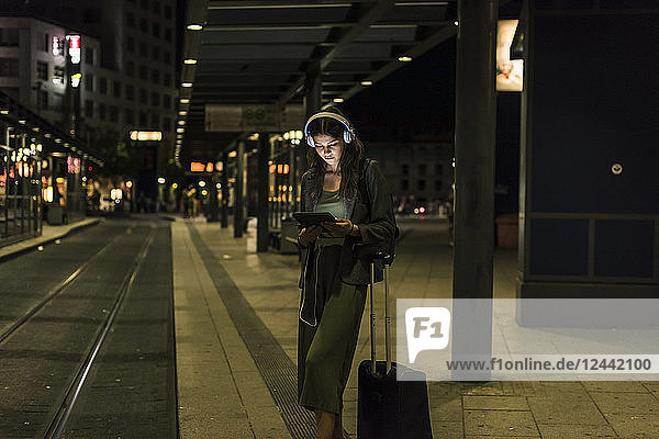 Young woman with headphones and tablet waiting at station by night