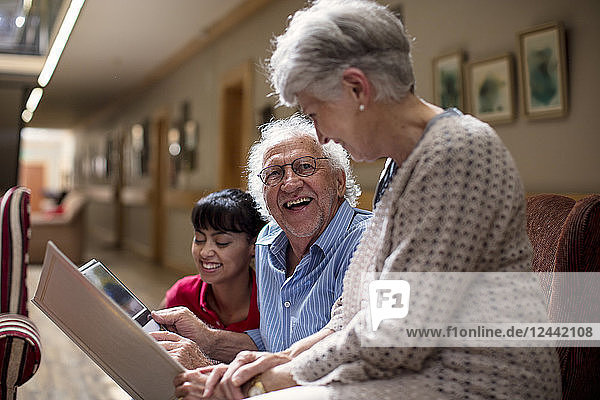 Nurse teaching seniors in retirement home  how to use laptop