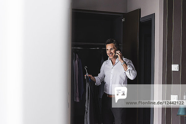Smiling businessman on cell phone at home getting dressed