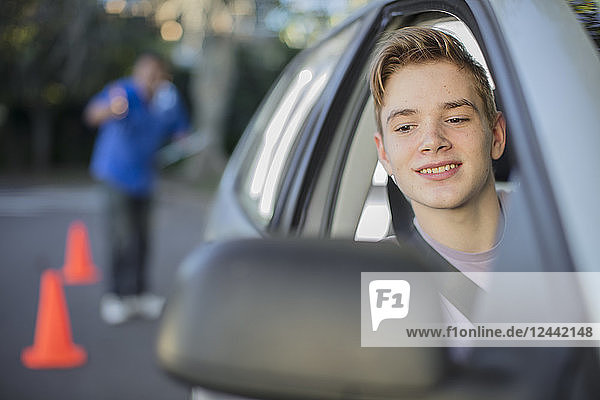 Learner driver learning to drive looking at wing mirror of a car
