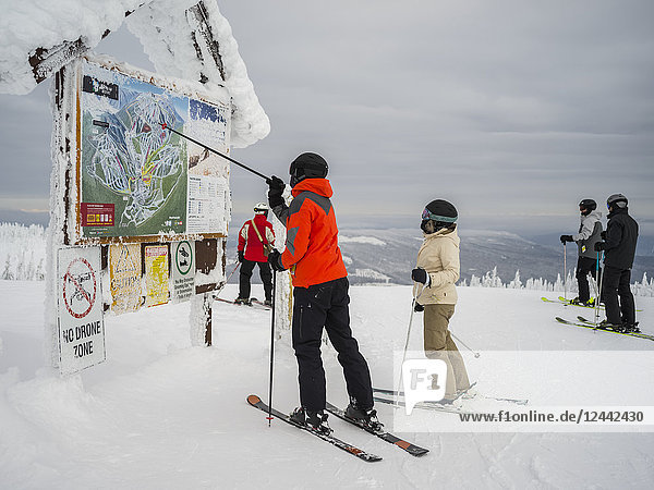 Skiers look at a map at Sun Peaks ski resort; Kamloops  British Columbia  Canada