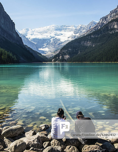 Two people distracted by looking at their smart phones while sitting along the shoreline of Lake Louise; Alberta Canada