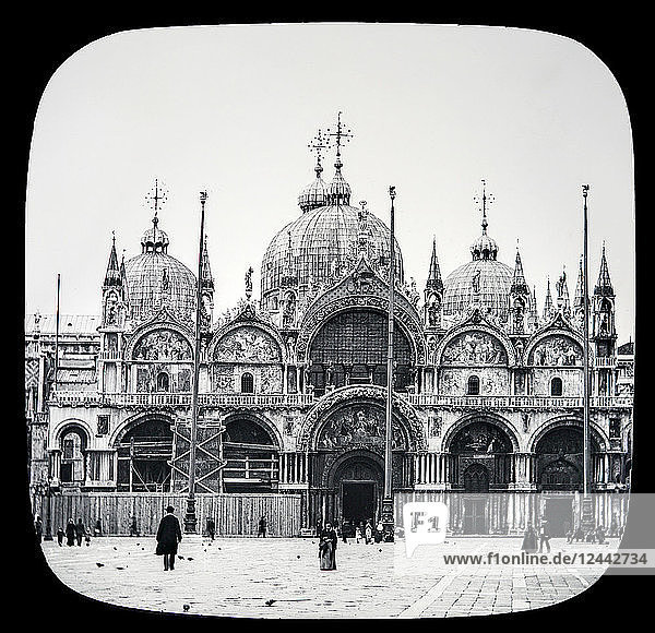 St. Mark's Cathedral  Venice circa 1900 on a magic lantern slide  photographs created in 1888 by Joseph John William. First built in the ninth century  but burned in the century following. It was again rebuilt during parts of the tenth and eleventh centuries. The famous structure is of brick  adorned with the richest coloured marbles  and the architecture is Romanesque Byzantine  a style peculiar to Venice. The church is crowned with shining cupolas; Venice  Italy
