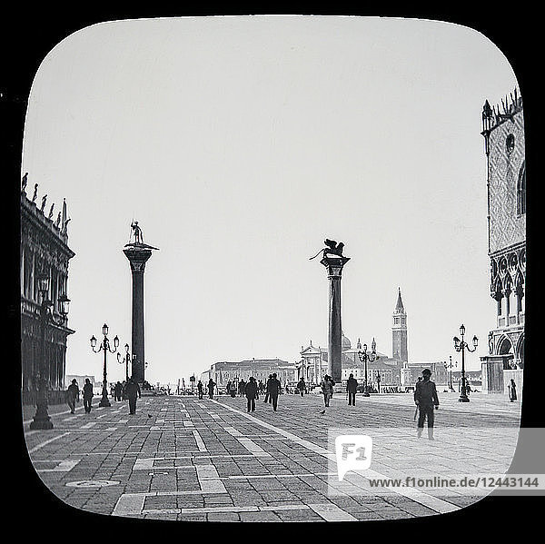 The beauties of Venice  circa 1900 on a magic lantern slide  photographs created in 1888 by Joseph John William. Small Piazza leading to the lagune with two famous granite columns brought by Doge Micheli from Syria in 1120  and erected here in 1180. One of these is surmounted by the winged lion of St. Mark  the emblem of the tutelary saint of Venice; the other bears the figure of St. Theodore  the patron saint before St. Mark supplanted him  on a crocodile. On the right is the Old Library and Mint; on the left is a portion of the Doge's palace. This portion of the Lagune  adjoining the Piazzetta  is the headquarters of the gondoliers; Venice  Italy
