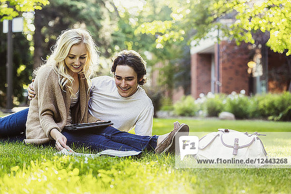 A young couple studying outdoors on the grass on the university campus and looking through a textbook while using a tablet  Edmonton  Alberta  Canada