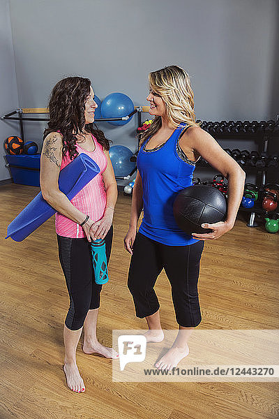 Two attractive middle-aged women talking to each other after working out at a fitness class in a gym  Spruce Grove  Alberta  Canada