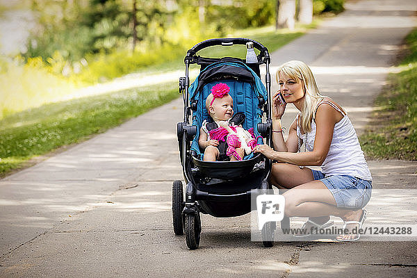A beautiful young mother taking her baby daughter out for a walk using a stroller in a park with a lake on a warm sunny day and stopping to take a call on her cell phone  Edmonton  Alberta  Canada