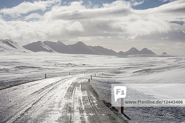 The Ring Road in Iceland goes off into the distance through the snowy North Iceland landscape  Iceland