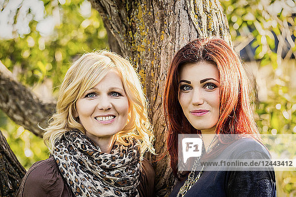 A beautiful mother and daughter pose for a picture in a park just before sunset on a warm fall day  St. Albert  Alberta  Canada