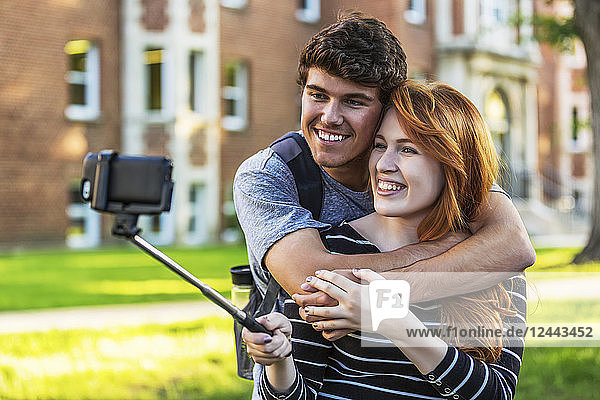 A young couple standing together in a university campus and taking a selfie with a smart phone on a selfie stick  Edmonton  Alberta  Canada