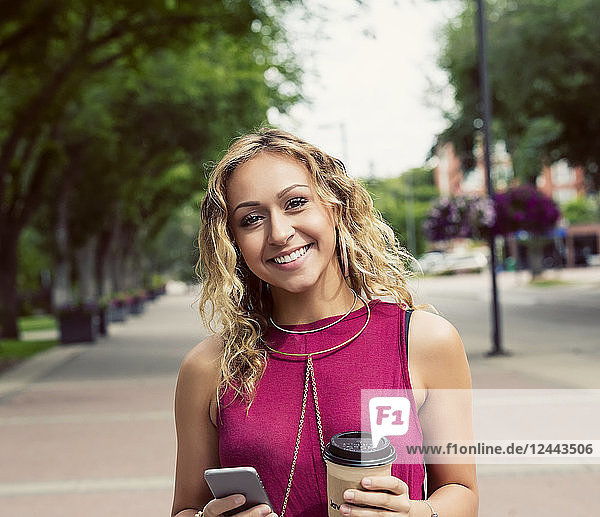 A young woman looks at the camera while walking down a street with a coffee near a university campus and texting on her smart phone  Edmonton  Alberta  Canada