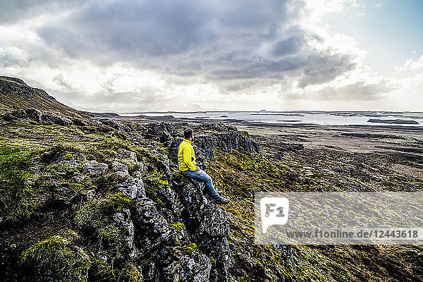 Man looks out over the ocean while sitting on a cliff; Iceland