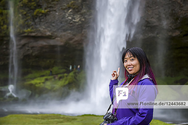 A young asian female hiker poses for a portrait at a waterfall  Iceland