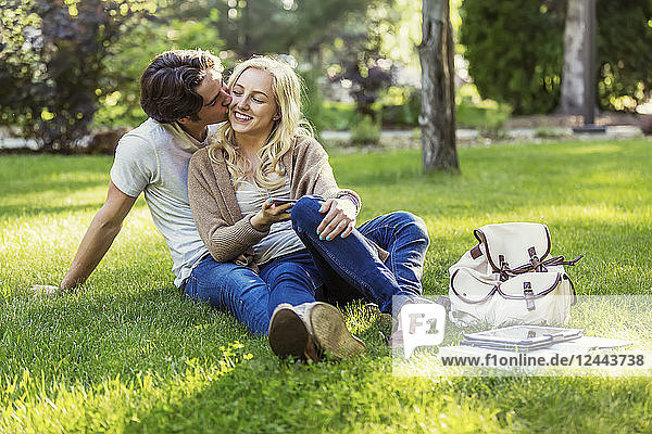 A young couple shares a romantic moment together sitting on the grass on the university campus  Edmonton  Alberta  Canada