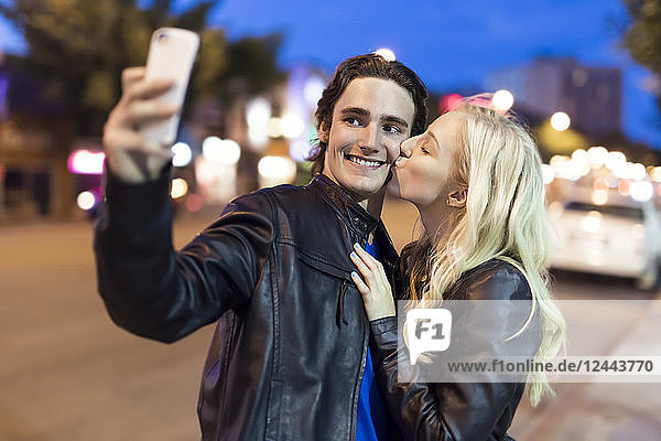 A young couple take a self-portrait with a smart phone as the female kisses the male on the cheek along a street at dusk  Edmonton  Alberta  Canada