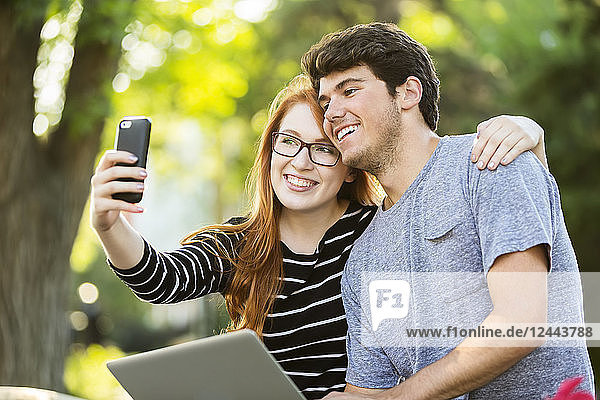 A young man and young woman taking a self-portrait on a smart phone  Edmonton  Alberta  Canada