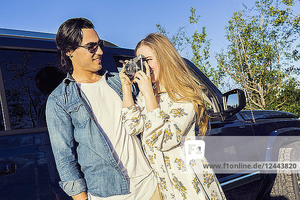 A young couple stands outside their vehicle on a road trip and the young woman takes a photograph with her camera  Edmonton  Alberta  Canada
