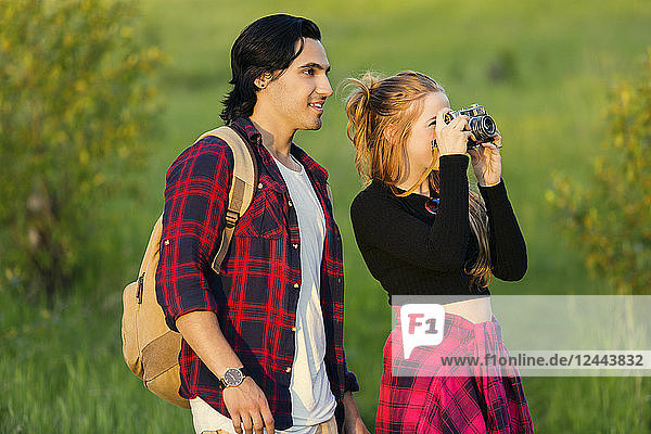 Young couple walking together in a city park pause to take a picture with a camera  Edmonton  Alberta  Canada
