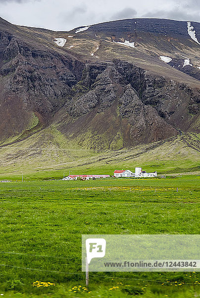 A large farmhouse estate property surrounded by vast fields in front of volcanic hillsides  Iceland