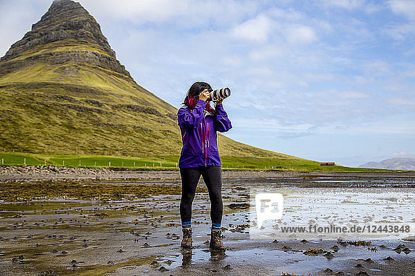 A female hiker stops on the beach at low tide to take a photo with an SLR camera in front of Kirkjufell Mountain in Snaefellsnes peninsula  Western Iceland  Iceland