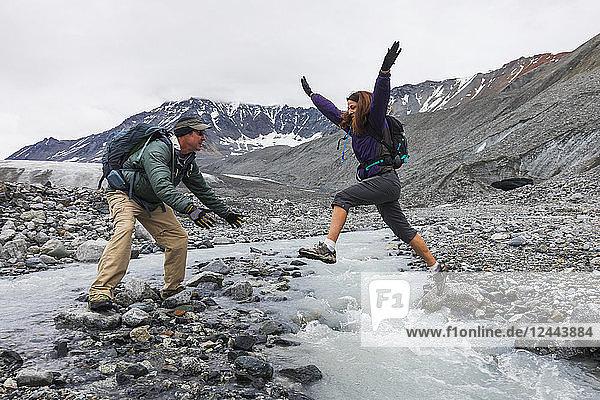 A wife jumps to her husband across an icy stream while hiking near Gulkana Glacier  Alaska  United States of America