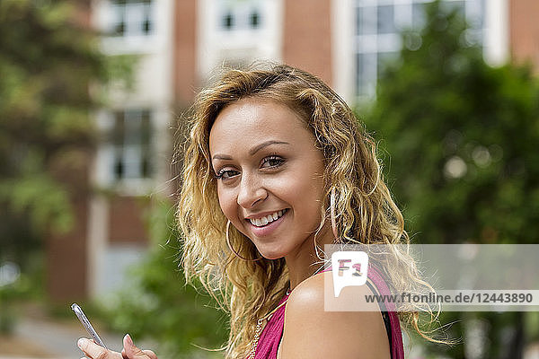 A beautiful young woman texting on her smart phone on a university campus and pausing to look at the camera  Edmonton  Alberta  Canada