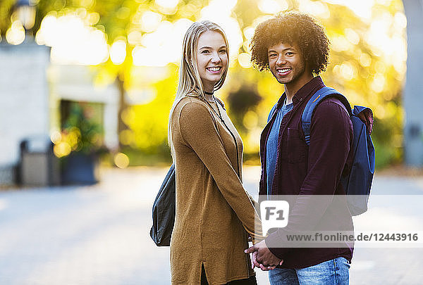 Boyfriend and girlfriend standing and holding hands on the university campus at sunset and posing for a picture  Edmonton  Alberta  Canada