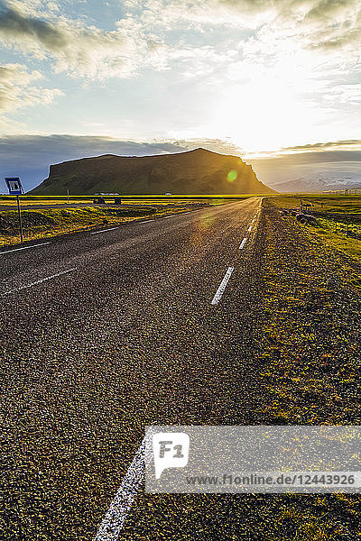 The sun sets behind the hills with a paved highway road leading into the sunset  Iceland