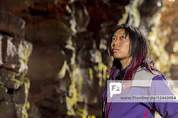 A side profile close-up of an asian female hiker looking upwards at the cave walls in a lava tube cave  Iceland