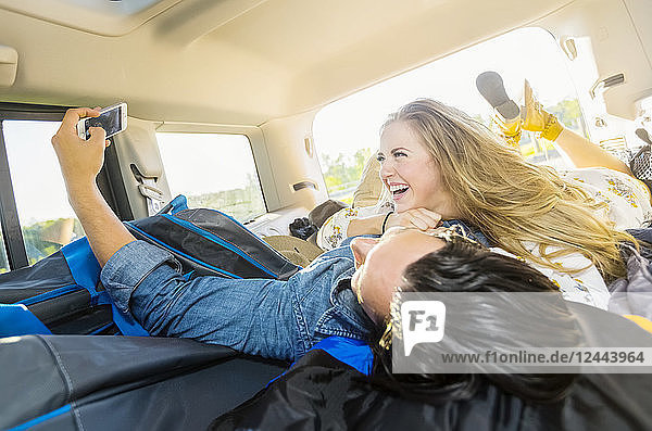 A young couple lays in the back of their vehicle during a road trip talking and laughing together and taking a self-portrait with their cell phone  Edmonton  Alberta  Canada