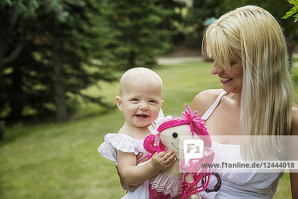 A beautiful young mom walking with her baby daughter while enjoying quality time together outdoors in a park on a warm summer day  Edmonton  Alberta  Canada