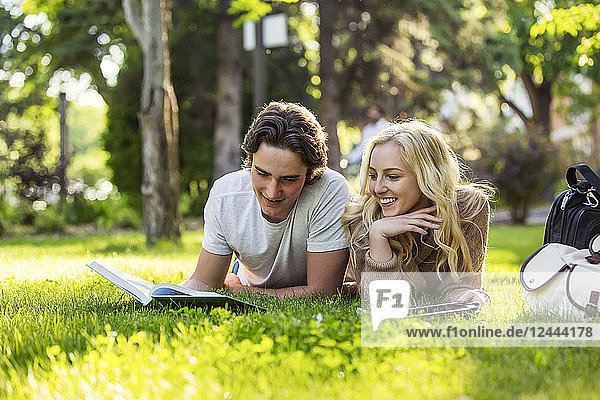 A young couple lays down studying on the grass on the university campus looking through a textbook and using a tablet  Edmonton  Alberta  Canada