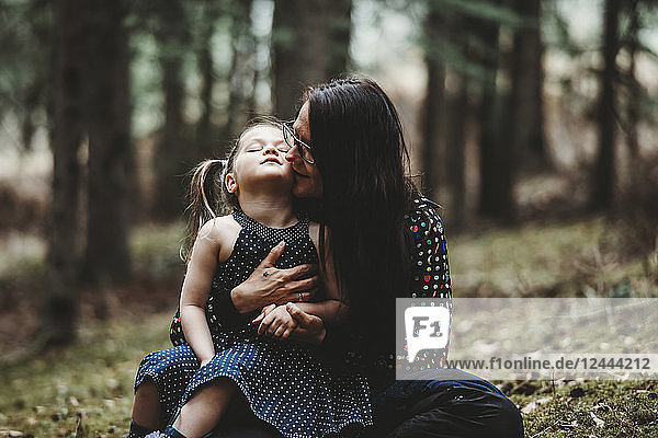 Portrait of a mother and young daughter in a forest  the young girl sitting in her mother's lap and looking up; Alberta  Canada